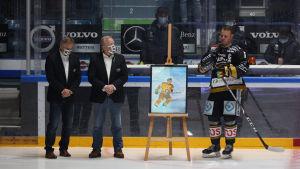 Lasse Kukkonen står på isen bredvid en tavla.