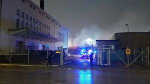Byggnad brinner. Räddningspersonal i bakgrunden.