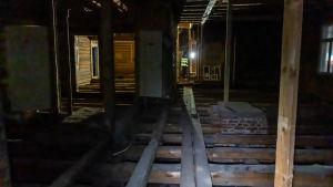 Inne i ett gammalt utblåst trähus.