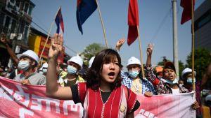 Demonstranter håller upp tre fingrar i luften.