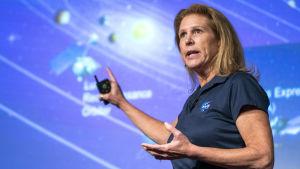Lori Glaze framför en illustration av solsystemet.