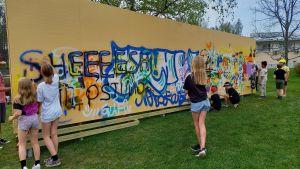 unga som målar på en gatukonstvägg.