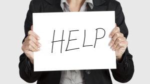 """En kvinna håller upp en skylt där det står """"HELP""""."""