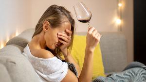 kvinna sitter i soffa med vinglas i handen, håller andra handen för ögonen