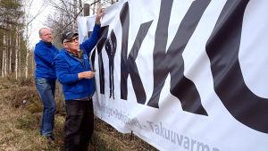 Daniel Björkstrand och Roy Smulter tar ner en fem meter lång banderroll med reklam för Mikko Ollikainens kandidatur för SFP i riksdagsvalet i Vasa valkrets.