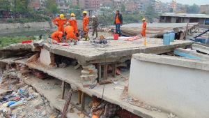 Räddningsarbetare letar efter överlevande i ett rasat flervåningshus.