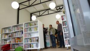 Filialbibliotek, ljusa bokhyllor och tre män som står och pratar, en håller papper i handen.