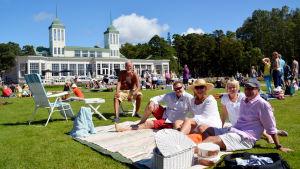 Människor sitter på picknickfiltar i Casinoparken i Hangö.