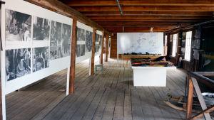 Svartvita bilder hänger på en utställning på en gammal vind.