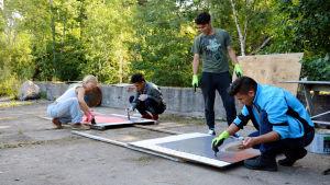 Människor står och målar på olika plakat.