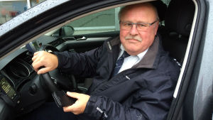 En man sitter i en taxibil. Han heter Stig-Erik Holmström och är taxichaufför.