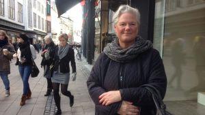 Rike Olsen, en dam i övre medelåldern, framför ett skyltfönster på en gågata, Köpenhamn.