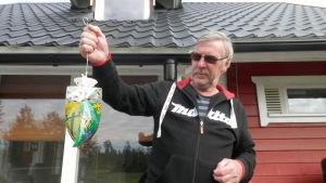 Jouko Liinamaa i Fäboda håller upp en flugfångare fylld med ett kilo flugor