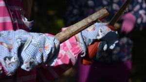 Barn täljer en käpp.