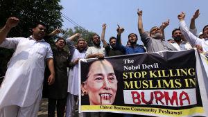 """""""Nobel-djävulen, sluta döda muslimer i Burma"""" står det på banderollen som hölls upp av demonstranter i Pakistan den 7 september."""