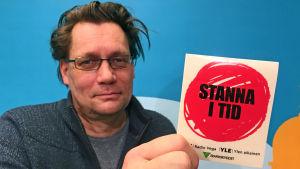 Mikael Kokkola visar upp ett klistermärke från kampanjen Stanna i tid.