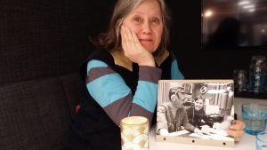 Kvinna håller upp svartvitt fotografi