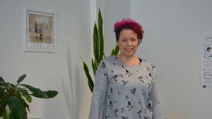 Bild på språkbadslärare Marjo Kekki som poserar i sitt klassrum.