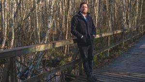 Henrik Håkansson nojaa puista kaidetta vasten, takana kosteikko, koivuja, kokokuva.