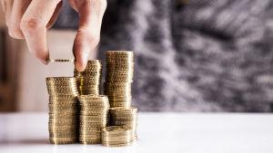 En hand lägger mynt i staplar.
