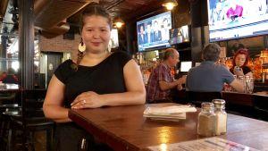 Helena Jonsson tar kort ståpaus vid ett restaurangbord,i bakgrunden kunder och övrig personal