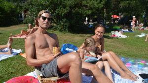 Man, kvinna och barn på badstrand.