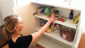 Intill matsvinnskylskåpet i Arabiastranden finns också ett skåp för torrvaror. En kvinna sätter in en burk med babymat i skåpet.