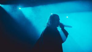 Rap-artisti Paperi T esiintyy Tampereen Pakkahuoneella sinertävässä valossa.