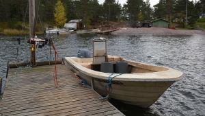 Den vitgula fiskebåten är fastbunden vid träbryggan.
