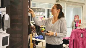 En kvinna radar upp produkter i en butik i ett köpcentrum. Runt henne finns kläder.