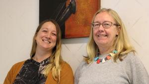 Två kvinnor står framför en tavla. Kvinnan till vänster är kring 40 år och har ljust långt hår. Kvinnan till höger är kring 50 år. Hon har blont axellångt hår och glasögon.