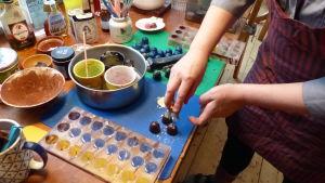 Två kvinnohänder som jobbar med choklad i ett kök. Hon stänker livsmedelsfärg över praliner.