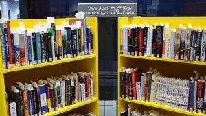 Reserverade låneböcker i bokhyllor i bibliotek.