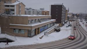 En gata med bilar och en affärslokal i ett vinterlandskap.