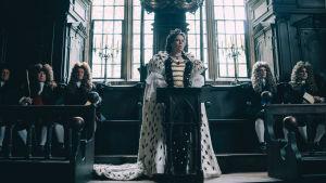Olivia Colman puhujapöntössä kuningatar Annen roolissa. Kuva elokuvasta The Favourite.