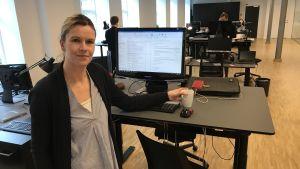 Lotta Nymann-Lindegren vid sin dator i ett öppet kontor.