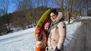 Mor och dotter står och ler för kameran vid toppen av borgbacken i Borgå