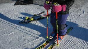 En utförsåkare står färdig med skidor och stavar påsatta.