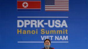 Vietnamesisk kvinna framför mötesskylt