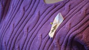 Ett rosa band till förmån för bröstcancerforskning är fäst på en lila tröja.