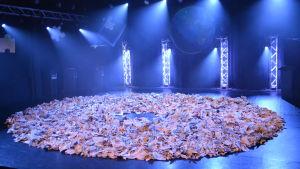 Tidningar på golvet på Tryckeriteaterns scen.