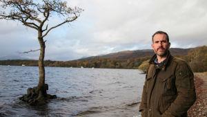 Mies seisoo rannnalla ja katsoo kameraan. Taustalla näkyy vedessä seisova yksinäinen puu.