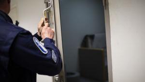 poliisi sulkemassa tutkintavankilan sellin ovea