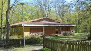 En bred, men ganska låg gulmålad träbyggnad ute i grön och lummig natur.