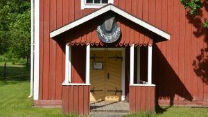 """Ett gammalt trähus målad i rödmylla med vita detaljer. Finns en skylt  på farstutrappan där det står """"Gillesgården""""."""