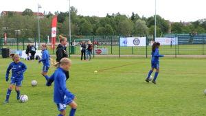 Fotbollstränaren Sanna Malaska, klädd i svart, ser på då hennes juniorlag värmer upp, klädda i blått.