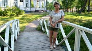 En kvinna står på en vit träbro i en park.