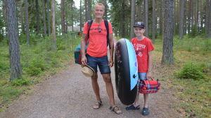 Far och son på stig vid badstrand i Borgå.