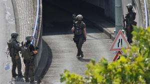 Tungt beväpnade poliser står vid en ingång till en parkeringshall.