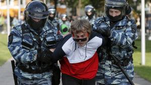 Kravallpoliser släpar iväg en rödklädd demonstrant.